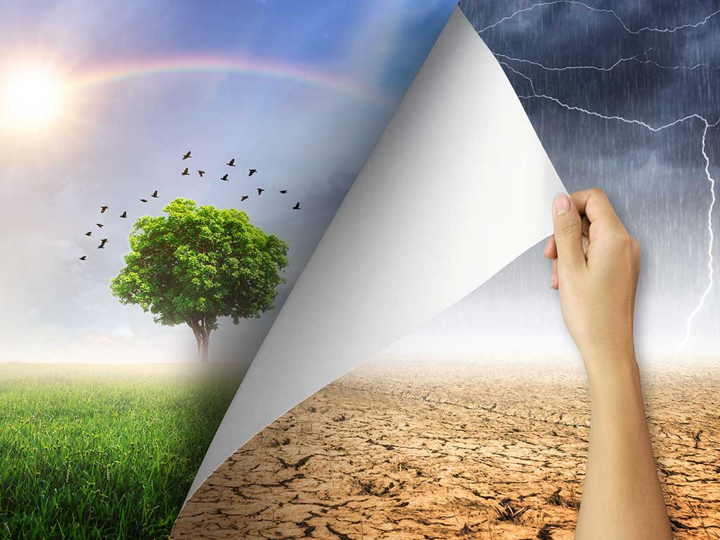 Hand pealing picture of stormy skies with rain, dark clouds, lightning over a parched desert landscape to reveal an image below with green meadow, a tree, birds flying above in a sunny, blue sky with a rainbow
